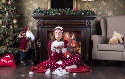A mulher bonita nova em pijamas vermelhos da roupa da casa do Natal senta-se sob uma árvore de Natal perto de uma chaminé e funde fotografia de stock