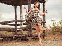 Mulher bonita nova em salto lisonjeiramente do vestido floral do verão Fotografia de Stock Royalty Free
