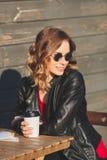 Mulher bonita nova em um café bebendo do casaco de cabedal preto Foto de Stock Royalty Free