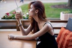 A mulher bonita nova em um chapéu branco senta-se em um café em uma rua do verão e bebe-se o café Fotografia de Stock Royalty Free