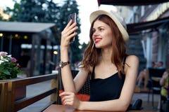 A mulher bonita nova em um chapéu faz uma foto no telefone que senta-se em um café em uma rua na cidade foto de stock royalty free