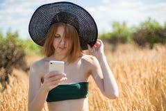 A mulher bonita nova em um chapéu usa um smartphone no dia ensolarado no campo Imagens de Stock