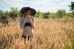 A mulher bonita nova em um chapéu usa um smartphone no dia ensolarado no campo Foto de Stock