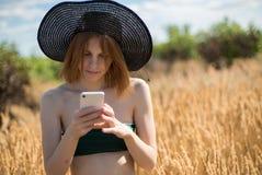 A mulher bonita nova em um chapéu usa um smartphone no dia ensolarado no campo Fotos de Stock Royalty Free