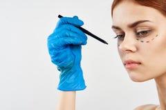 Mulher bonita nova em um fundo branco, contorno facial, cirurgia plástica fotos de stock