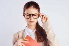 A mulher bonita nova em um fundo claro nos vidros guarda um caderno, professor, esforço, emoções, retrato fotografia de stock