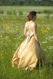Mulher bonita nova em um vestido amarelo no campo imagens de stock royalty free