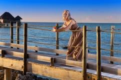 A mulher bonita nova em um vestido longo na estrada de madeira sobre o sea.portrait contra o mar tropical Fotos de Stock