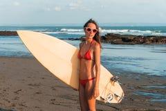 A mulher bonita nova em vidros vermelhos do biquini e de sol realiza nas mãos uma ressaca na praia do oceano no por do sol Imagem de Stock Royalty Free