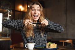 A mulher bonita nova emocional que senta-se no café dentro toma uma foto de seu café da manhã pelo telefone celular fotos de stock