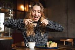 A mulher bonita nova emocional que senta-se no café dentro toma uma foto de seu café da manhã pelo telefone celular fotos de stock royalty free