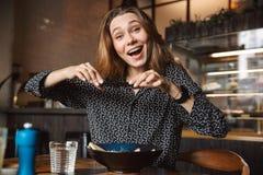 A mulher bonita nova emocional que senta-se no café dentro toma uma foto de seu café da manhã pelo telefone celular imagem de stock