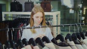 A mulher bonita nova escolhe o vestido na loja de roupa vídeos de arquivo