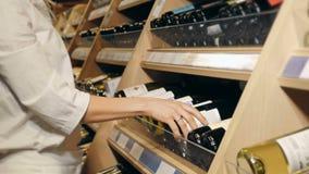 A mulher bonita nova escolhe o vinho no supermercado Fotos de Stock