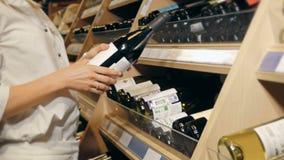 A mulher bonita nova escolhe o vinho no supermercado Imagem de Stock