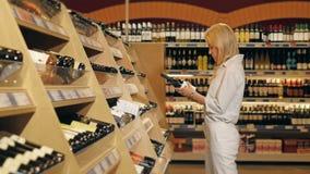 A mulher bonita nova escolhe o vinho no supermercado Fotografia de Stock Royalty Free