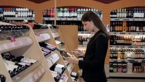 A mulher bonita nova escolhe o vinho no supermercado Morena na loja alcoólica Fotografia de Stock Royalty Free