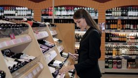 A mulher bonita nova escolhe o vinho no supermercado Mulher de negócios na loja de vinho Fotografia de Stock