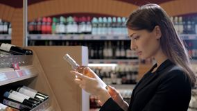 A mulher bonita nova escolhe o vinho no supermercado Mulher de negócios na loja de vinho Fotografia de Stock Royalty Free