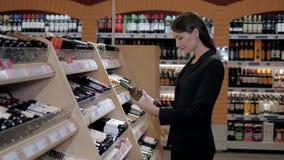 A mulher bonita nova escolhe o vinho no supermercado Mulher de negócios na loja de vinho Imagem de Stock