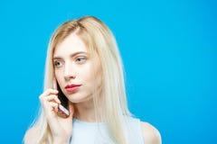 A mulher bonita nova escuta alguém que usa seu Smartphone no fundo azul Menina bonito com o móbil no estúdio Fotos de Stock