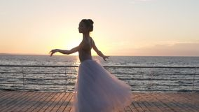 A mulher bonita nova está dançando o tutu branco vestindo no nascer do sol ou no por do sol Executando o pas clássico do bailado  video estoque