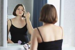 A mulher bonita nova está fazendo a composição e está olhando no espelho Fotografia de Stock Royalty Free
