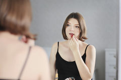 A mulher bonita nova está fazendo a composição e está olhando no espelho Foto de Stock