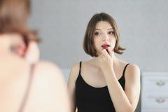 A mulher bonita nova está fazendo a composição e está olhando no espelho Imagens de Stock Royalty Free