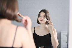 A mulher bonita nova está fazendo a composição e está olhando no espelho Imagem de Stock