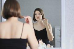A mulher bonita nova está fazendo a composição e está olhando no espelho Imagens de Stock