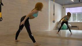 A mulher bonita nova está fazendo exercícios em uma sala da aptidão filme