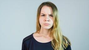 A mulher bonita nova está irritada em um fundo branco Mulher nova irritada foto de stock