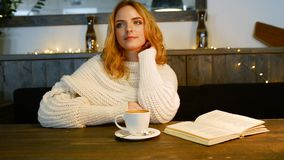 A mulher bonita nova está lendo um livro no café É de sorriso e de apreciação o aroma do café filme