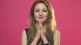 A mulher bonita nova está rezando no fundo cor-de-rosa video estoque
