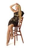 A mulher bonita nova está sentando-se na cadeira de madeira alta. imagens de stock