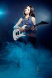 A mulher bonita nova está sentando-se na fase com uma guitarra. Névoa sobre fotografia de stock royalty free