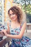 A mulher bonita nova está sentando-se no banco perto do centro de negócios Sorri, olhar enviado à câmera Vestindo um floral azul foto de stock royalty free