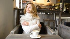 A mulher bonita nova está sorrindo no café e está apreciando o aroma do café vídeos de arquivo