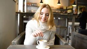 A mulher bonita nova está sorrindo no café e está apreciando o aroma do café video estoque