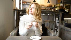 A mulher bonita nova está sorrindo no café e está apreciando o aroma do café filme