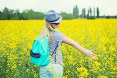 A mulher bonita nova est? andando ao longo de um campo de floresc?ncia em um dia ensolarado imagem de stock