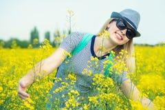 A mulher bonita nova est? andando ao longo de um campo de floresc?ncia em um dia ensolarado foto de stock