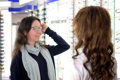 A mulher bonita nova est? tentando vidros do olho sobre em uma loja do eyewear com ajuda de um assistente e de partes de loja em  fotos de stock