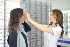 A mulher bonita nova est? tentando vidros do olho sobre em uma loja do eyewear com ajuda de um assistente e de partes de loja em  imagens de stock