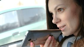 A mulher bonita nova fala uma mensagem da voz em um telefone celular que senta-se no carro e nos sorrisos filme