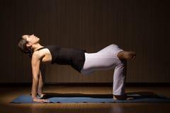 A mulher bonita nova faz a ioga que levanta, baixa chave fotos de stock