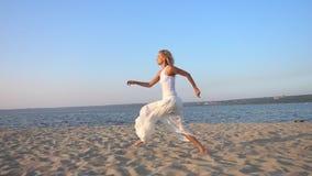 mulher bonita nova feliz que corre e que salta na praia video estoque