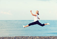 Mulher bonita nova feliz que salta na praia no mar imagens de stock royalty free