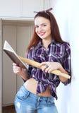 A mulher bonita nova lê o livro de receitas para a receita Foto de Stock Royalty Free